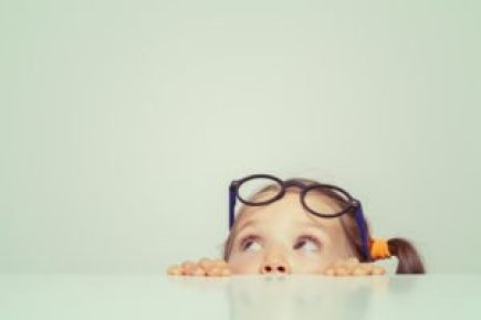 Little Girl with Glasses Looking Up at Big Table