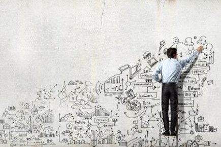 Businessman on Ladder Drawing Business Concepts on Wall
