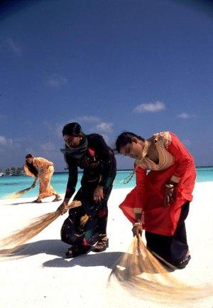 Women sweeping beach Maldives