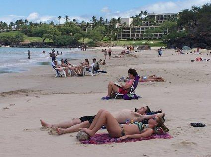Kathy reading on Hapuna beach with Hapuna Prince Hotel in background