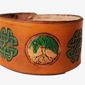 a hand cut leather cuff with tree of life motif and celtic knot stamps