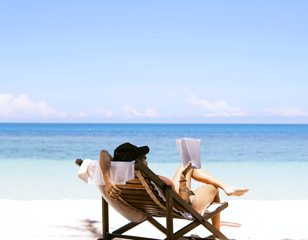 Woman Sitting In Lounge Chair On A Tropical Beach Reading A Book