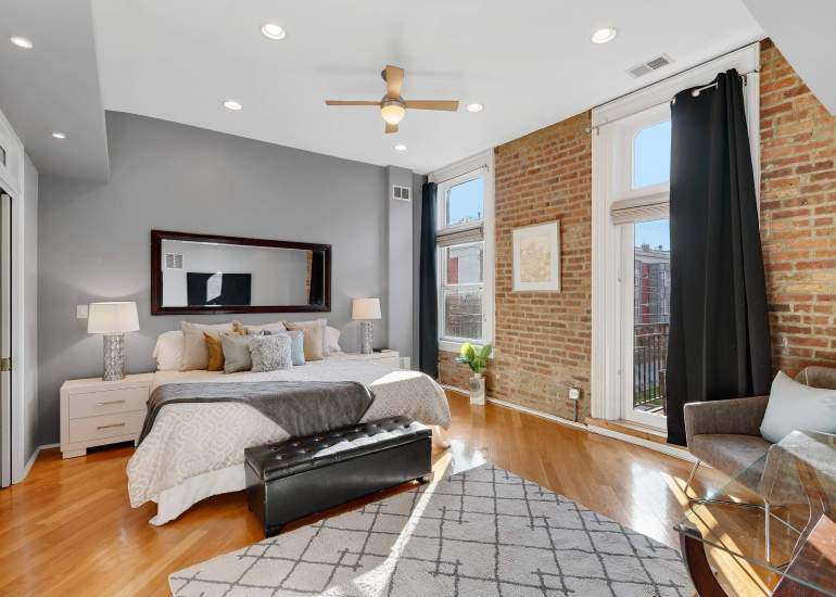 Beautiful master bedroom (primary bedroom) real estate photo, with the exposed brick wall