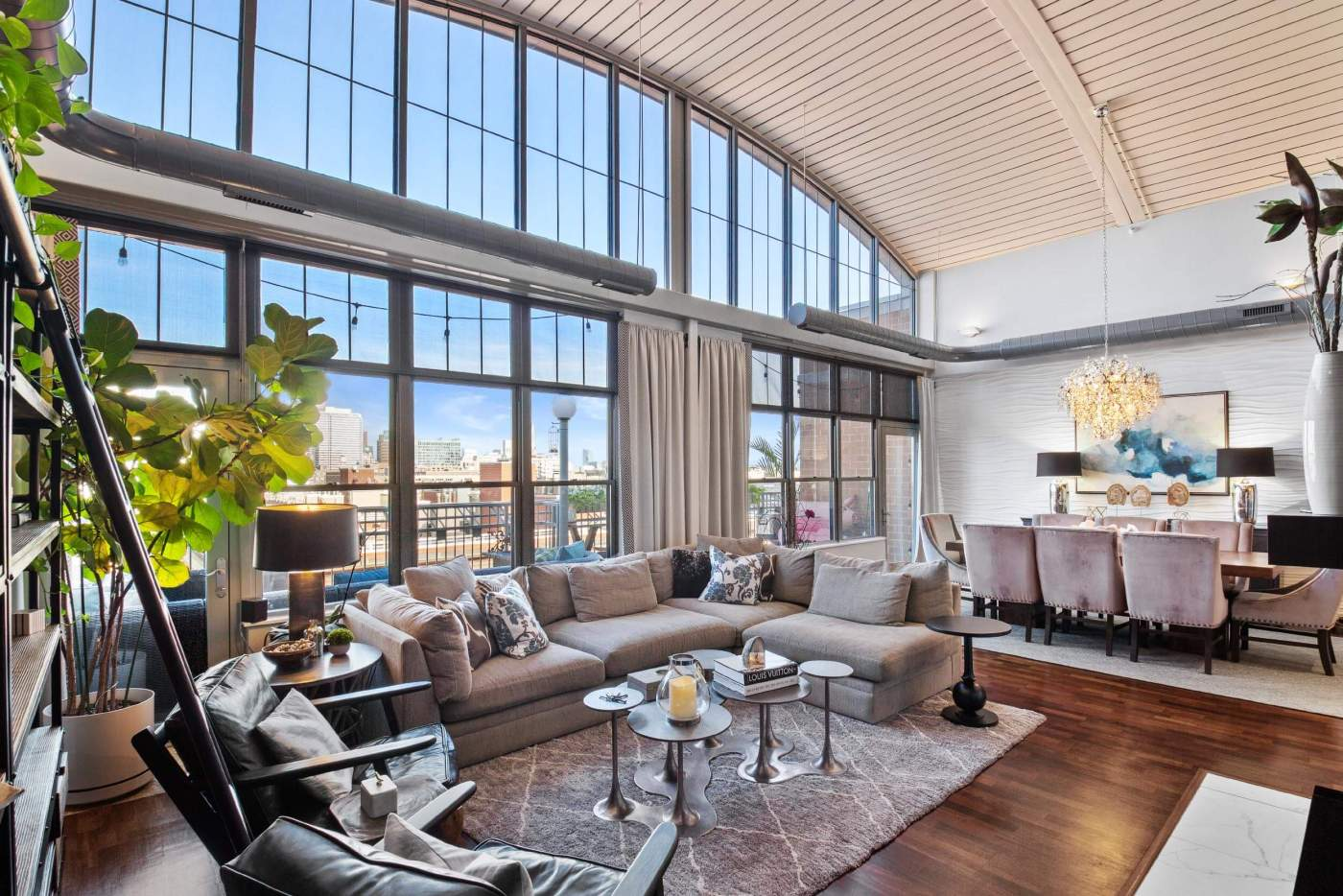 Real estate photo of the large living room with the vaulted ceiling and high windows with the views of the Chicago downtown