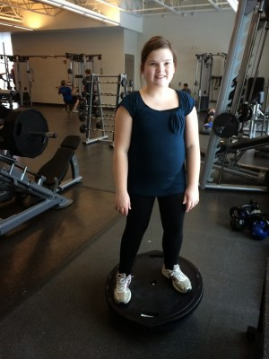 tween_girl_balancing_on_inverted_balance_ball_at_gym