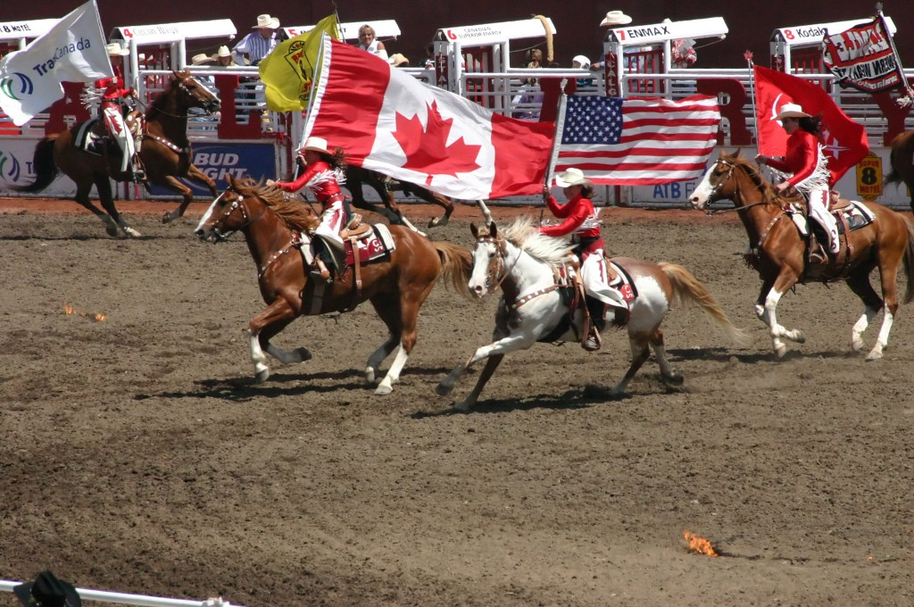 CALGARY CANADA JULY 2004 - Cowgirls galloping on horseback carrying flags Calgary Stampede Alberta Canada