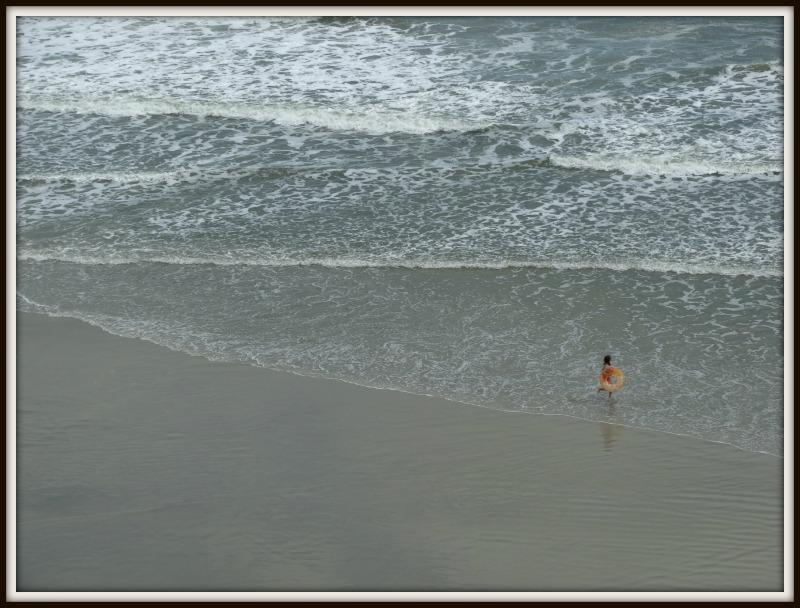 Daytona Beach shore with a child playing near water's edge
