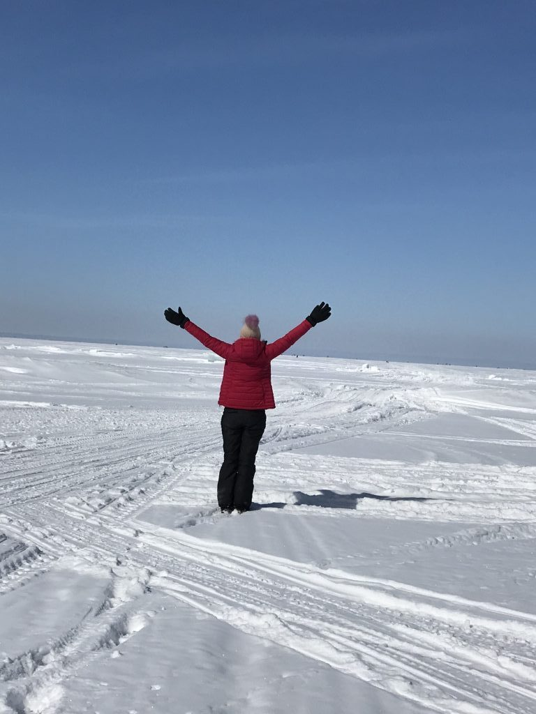 lake_simcoe_lady_standing_on_snow_outstretched_arms