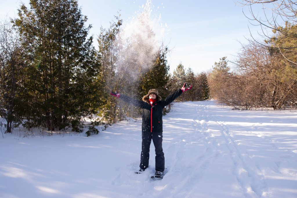 girl_tossing_snow_in_air_surrounded_by_trees