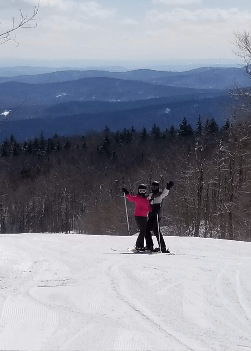 couple_skiing_together_arms_raised_posing_against_mountains