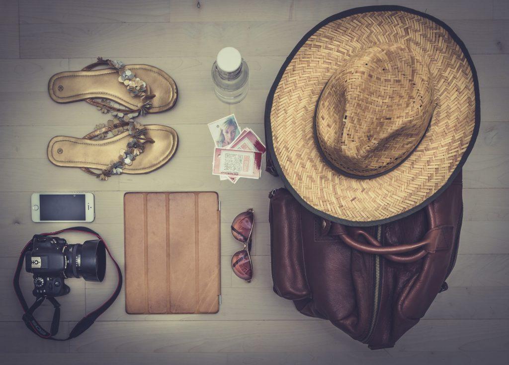 flat_lay_travel_items_hat_sandals_camera