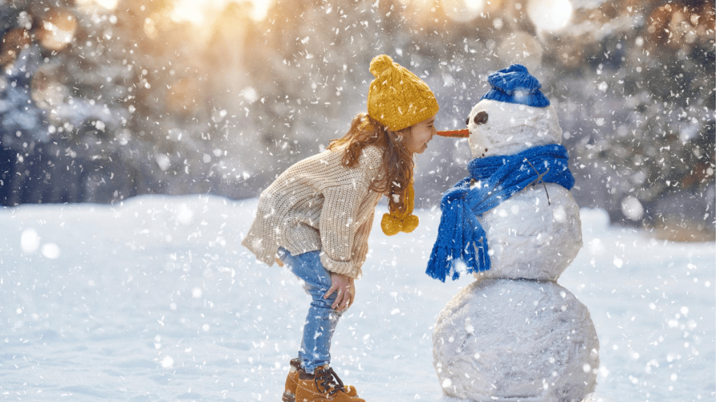 young girl standing in falling snow looking at her snowman with carrot nose and blue hat and scarf