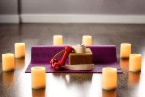 Purple yoga mat on a wooden floor topped with a yoga support block, small dumbbells and exercise strap surrounded by 8 white candles.