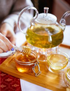 Glass teapot of herbs and water with woman taking honey from a nearby glass.