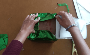 Taping the bottom of the gift bag to the bottom of the box.