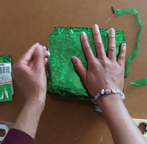 Taping the end of the gift bag to the bottom of the box.