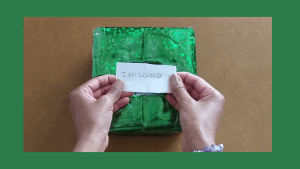 """Image of me holding an affirmation, """"I AM LOVING"""" over the green gift bag wrapped Positivity Affrimation Box."""