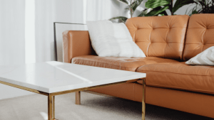 Brown sofa on right with white pillow leaning on arm rest placed in front of white tabletop with brown legged table.