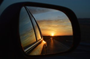 View of a rearview mirror of a car showing a sunset on the road.