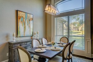 Dining room with dinner plates set in front of tall window and picture decor on the wall.