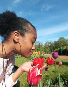 Netert Aset in a tulip garden smelling a tulip flower.