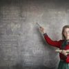Picture of a white woman with glasses on pointing to a chalkboard covered in writing.