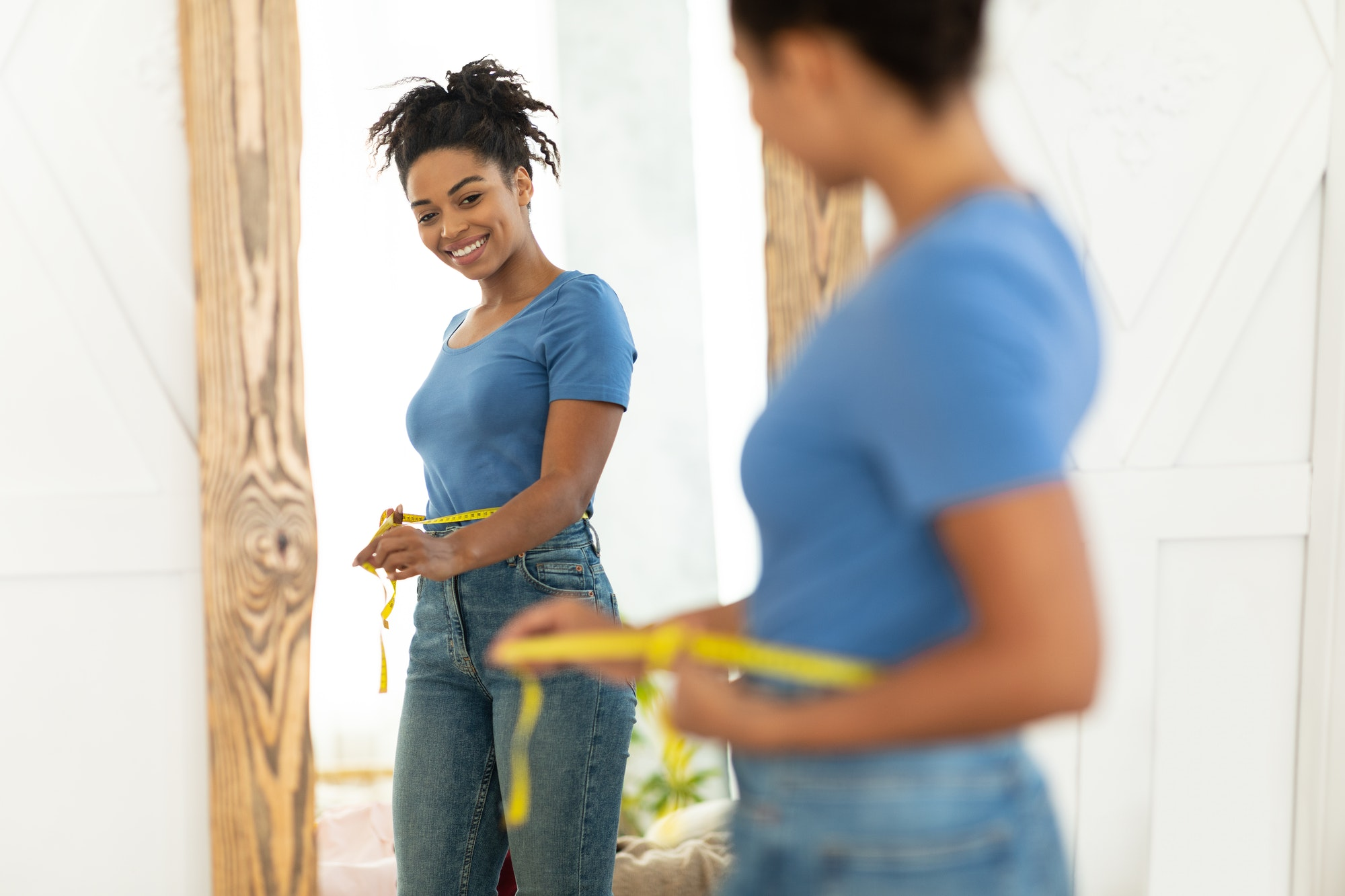 Cheerful Black Lady After Weight-Loss Measuring Waist With Tape Indoors