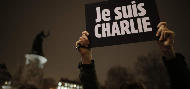 """A man holds a placard which reads """"I am Charlie"""" to pay tribute during a gathering at the Place de la Republique in Paris"""