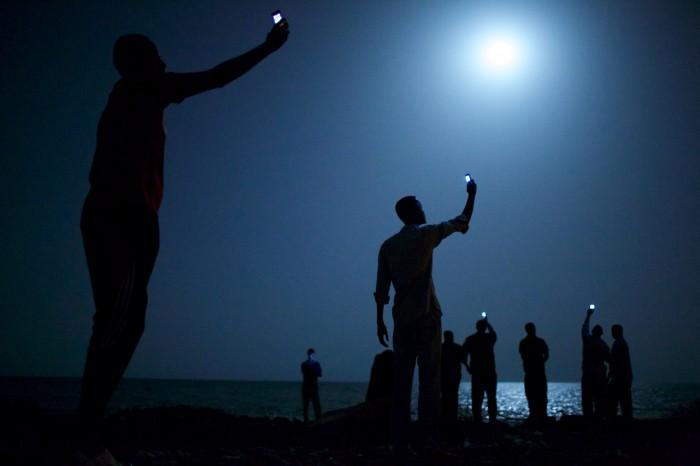 World Press Photo - Foto del año 2013 John Stanmeyer, USA, VII para National Geographic 26/02/2013, Djibouti Ciudad, Djibouti Inmigrantes africanos en la orilla de la ciudad de Djibouti en la noche, aumentando sus teléfonos en un intento de captar una señal de bajo costo de la vecina Somalia, un tenue vínculo con familiares en el extranjero. Djibouti es un punto de parada común para los migrantes en tránsito de países como Somalia, Etiopía y Eritrea, en busca de una vida mejor en Europa y el Medio Oriente.