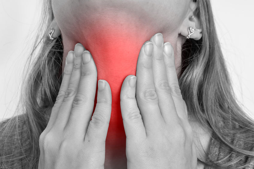 woman with throat sore is holding her aching throat - black and white photo