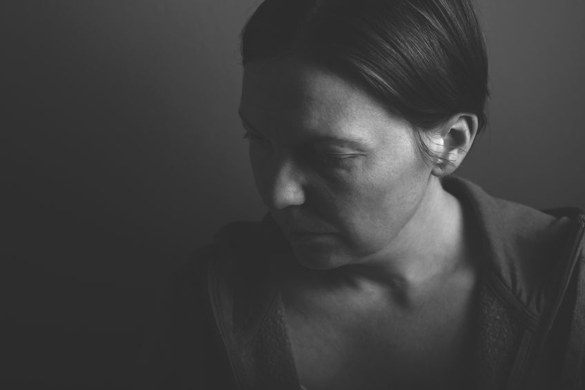 depressive woman, low key monochromatic portrait of sad adult female in dark room
