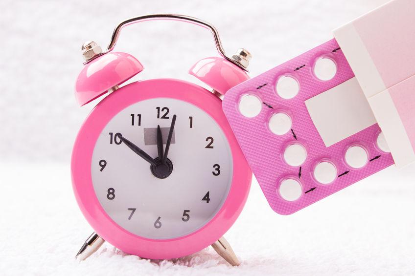 medicine and birth control. alarm clock and contraceptive pills