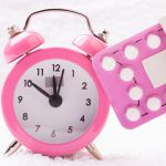 medicine and birth control. alarm clock and contraceptive pills