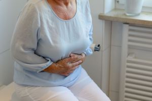 mid section of senior woman wearing white trousers and light blue blouse sitting on toilet holding stomach