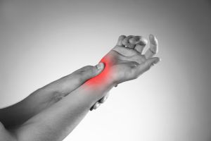 pain in the joints of the hands. carpal tunnel syndrome. black and white photo with red dot