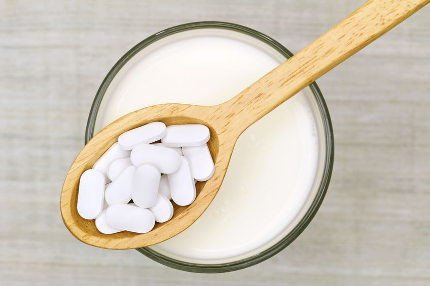 top view of a wooden spoon of white calcium carbonate tablets above a glass of fresh milk on a gray background