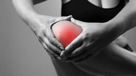 pain in the knee. pain in the human body on a gray background. black and white photo with red dot