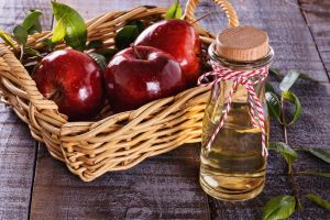 apple cider vinegar and red apples over rustic wooden background