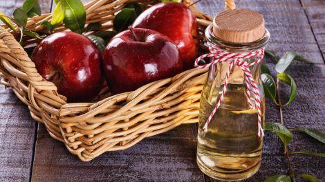 apple cider vinegar and red apples over rustic wooden background