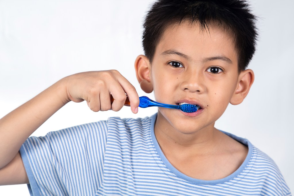 boy brushing teeth, on white