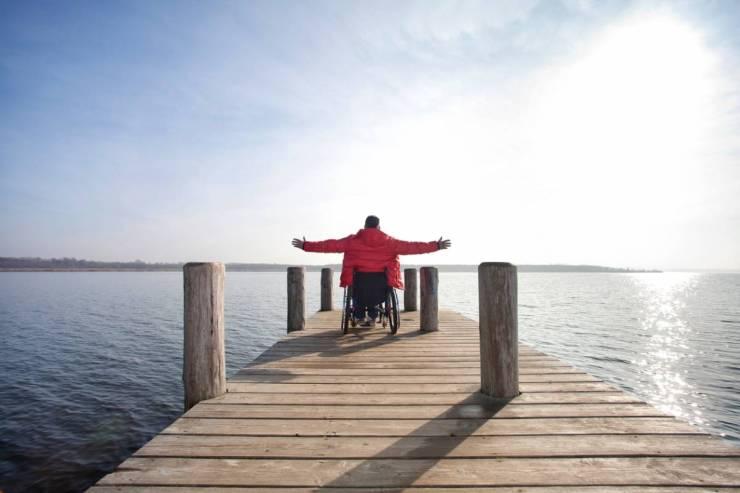 Voyage pour handicapé - homme en fauteuil roulant au bord de l'eau