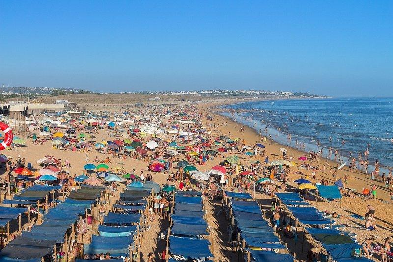 tourisme de masse plage bondée de monde - mer ou montagne cet été ?