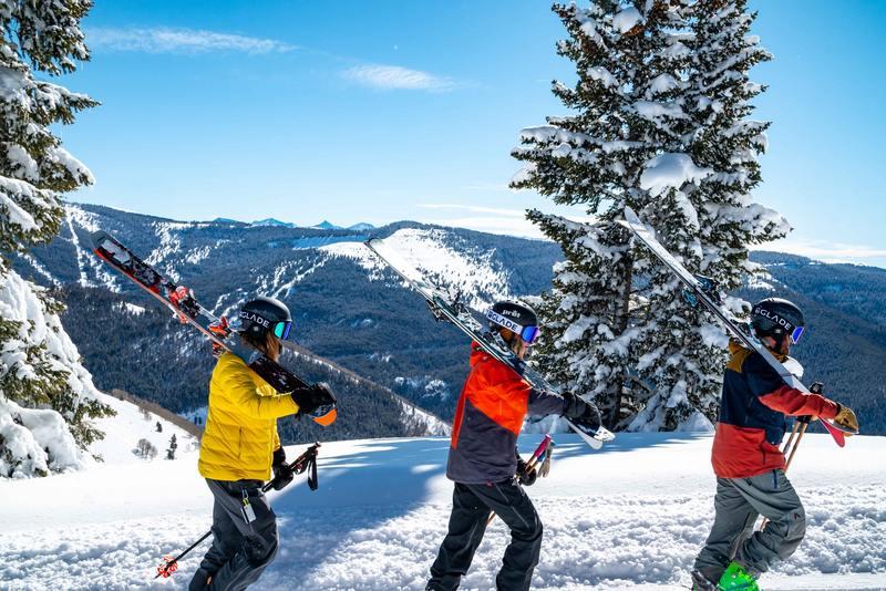 skieur portent leurs ski et marchent dans la neige