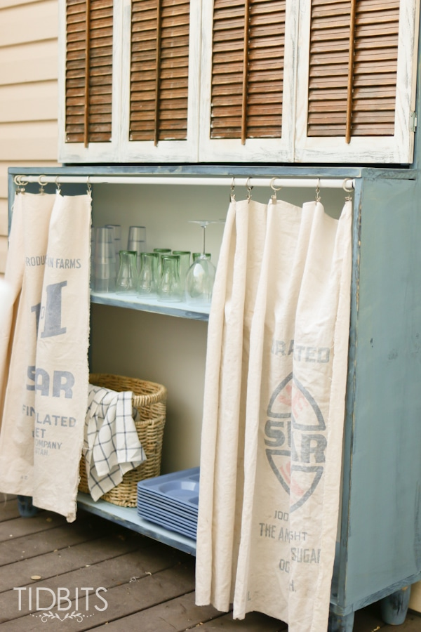 Vintage grain sacks used as curtains to conceal outdoor storage.  Deck makeover by TIDBITS.