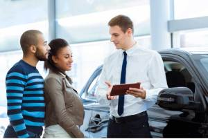 Picture of a car salesman talking to potential customers using a tablet in a showroom