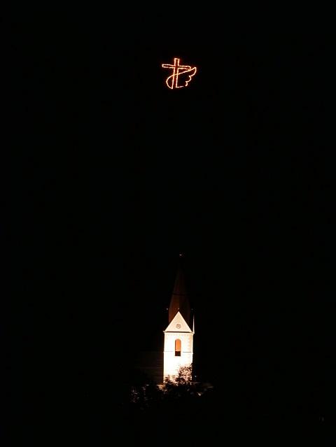 geflügeltes Feuerkreuz über dem Kirchturm von Schattwald