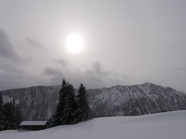 Blasse Wintersonne über Berg und Schnee