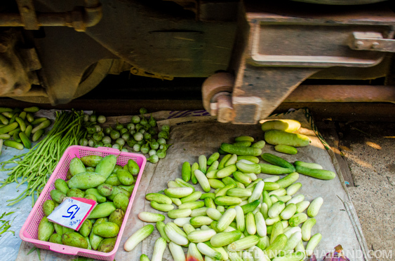 The train passes just above the produce at the Maeklong Railway Market