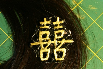 double-happiness hairpin, gold on black background