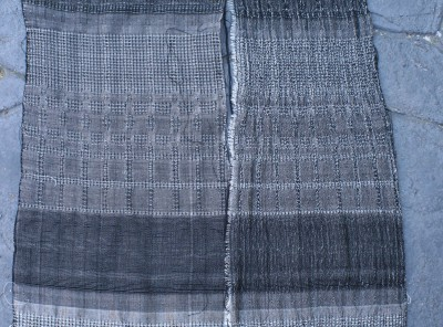 Plain weave and waffle weave, networked and allover pattern, with white overtwisted wool weft, beaten firmly.  Warp is black 60/2 silk sett at 40 epi.